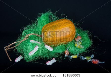 Big orange pumpkin in green grass with round multycolored sweets and candies in shape of teeth
