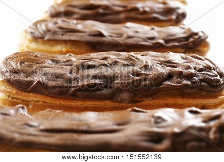 Delicious chocolate eclairs in row on white background, closeup