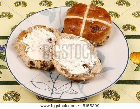 Buttered hot cross bun on a plate 1