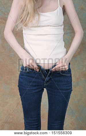 Young girl trying to zip up tight blue jeans