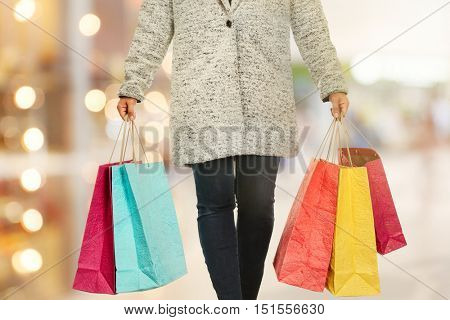 Woman with shopping bags on blurred market background. Christmas shopping concept.