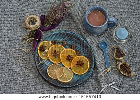 Flatlay. Dried citrusfruit on a blue plate, fresh juice in a blue cup lying on a knitted background