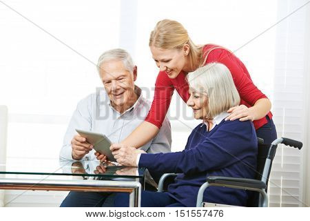 Happy senior couple learning how to use tablet computer with granddaughter