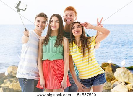 Group of young people taking selfie on blurred ocean background.