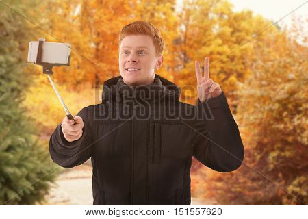 Young man taking selfie on blurred nature background.
