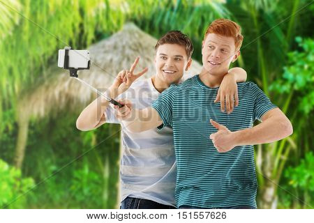 Young happy men taking selfie on blurred jungle background.