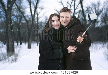 Young happy couple taking selfie on blurred nature background.