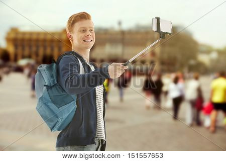 Young man taking selfie on blurred city square background.