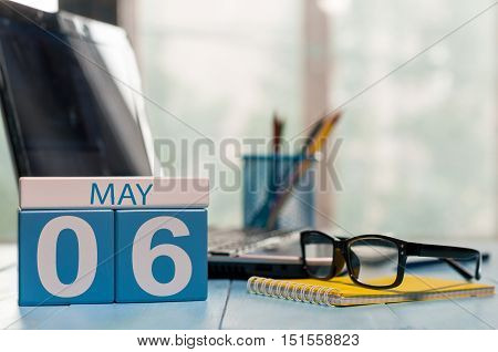 May 6th. Day 6 of month, calendar on business office background, workplace with laptop and glasses. Spring time, empty space for text.