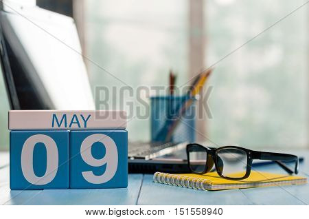 May 9th. Day 9 of month, calendar on business office background, workplace with laptop and glasses. Spring time, empty space for text.