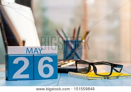 May 26th. Day 26 of month, calendar on business office background, workplace with laptop and glasses. Spring time, empty space for text.