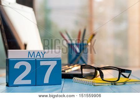 May 27th. Day 27 of month, calendar on business office background, workplace with laptop and glasses. Spring time, empty space for text.