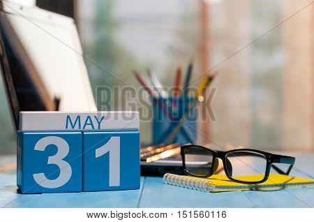 May 31st. Day 31 of month, calendar on business office background, workplace with laptop and glasses. Spring time, empty space for text.