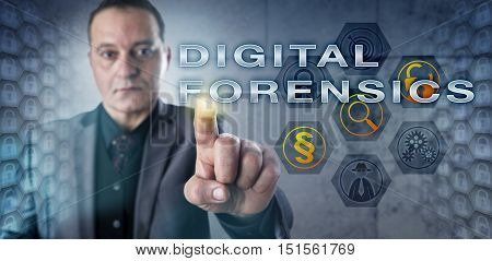 Mature male forensic investigator is pressing DIGITAL FORENSICS onscreen. Information technology metaphor and law enforcement concept for the forensic discipline of investigating digital media.