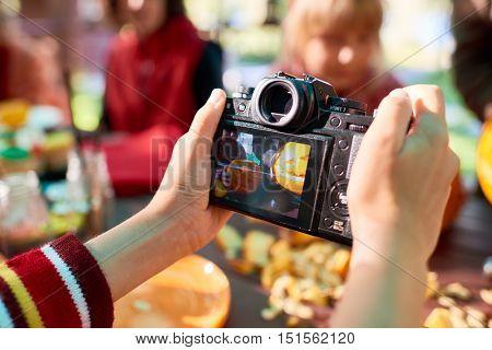 Close-up of man making photo of Jack o'Lantern with digital camera