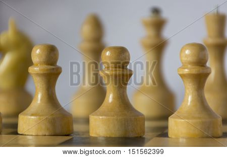 white wooden chess pieces chessman pawn knight castle queen king stand on a chessboard in the initial position in the foreground pawns