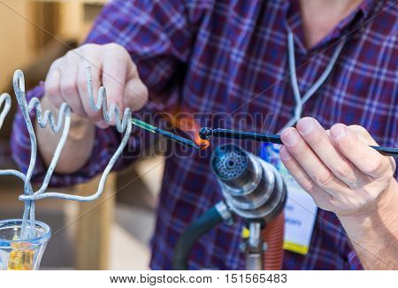 Zaporizhia/Ukraine- September  17, 2016: Family festival of homemade pickled canned vegetables and preserves. Closeup process of artistic glass blowing. Professional glass blower creating bird figure.