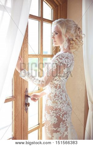 Beauty Portrait Of Elegant Bride In Wedding Dress Looking At Window, Indoors. Blonde Young Woman Wit