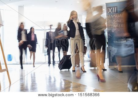Blurred motion of business people with luggage walking at convention center