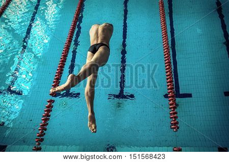 Swimmer man. Swimmings athlete after start jump to distance in waterpool.