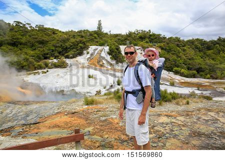 Young Active Father Hiking With Little Daughter In Back Carrier