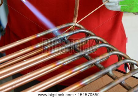 Worker at brazing copper pipes - close-up