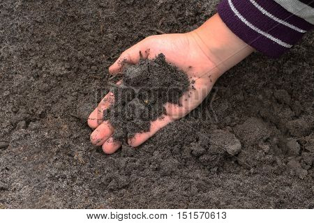 The child took the black earth.Fertile land , harvesting and planting crops.