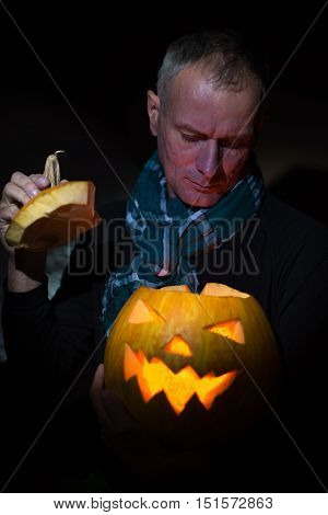 Halloween night. Man anxiously peering into the glowing pumpkin.