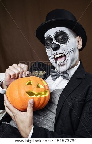 portrait of a man with a mexican calaveras makeup, wearing overcoat, waistcoat, bow tie and top hat, laughing and holding a carved pumpkin next to him