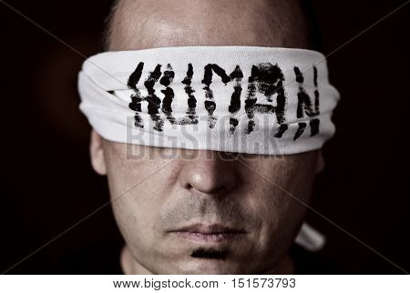 closeup of a young man with a blindfold in his eyes, with the word human handwritten in it
