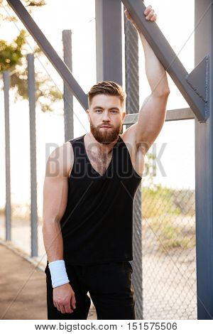 Handsome bearded young sportsman in sportswear and wristband standing outdoors