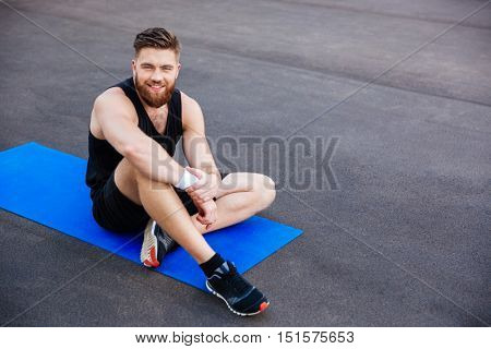 Smiling young bearded sports man sitting and resting on blue fitness mat outdoors