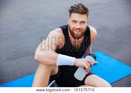 Close up porrait of smiling young sportsman with bottle of water sitting and relaxing outdoors