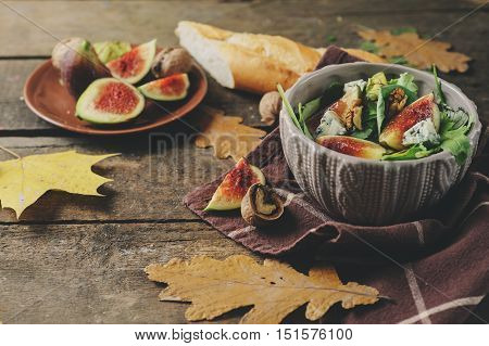 figs salad with blue cheese and ruccola on rustic wooden background. Homemade healthy food selective focus