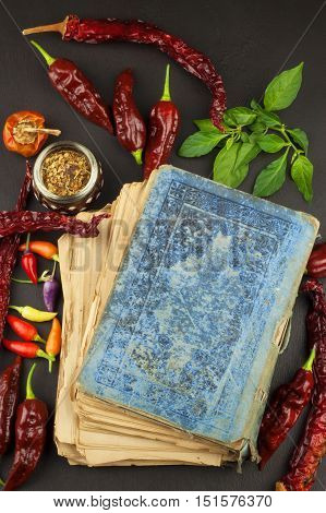 Cookbook and chillies. Recipe for spicy food. Mexican cuisine. Food preparation according to the old recipe book. Grandma's recipe book. Old recipes for cooking.