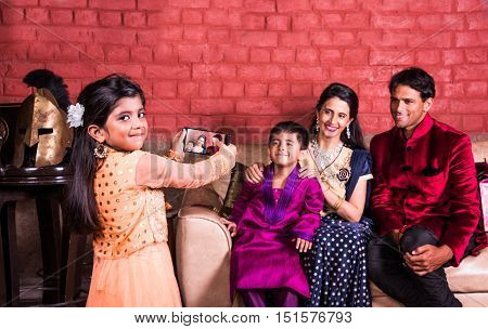 Happy family sitting on sofa or couch with daughter taking a picture of all using smartphone