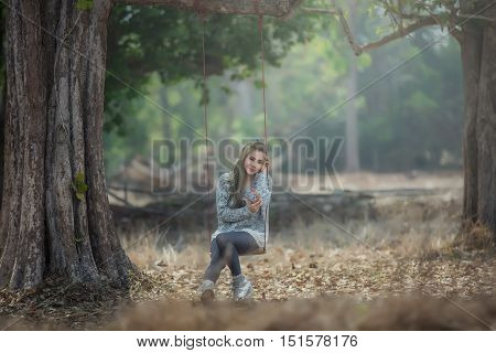 Portrait of a beautiful Asain Girl smiling and swinging in the forest Thailand