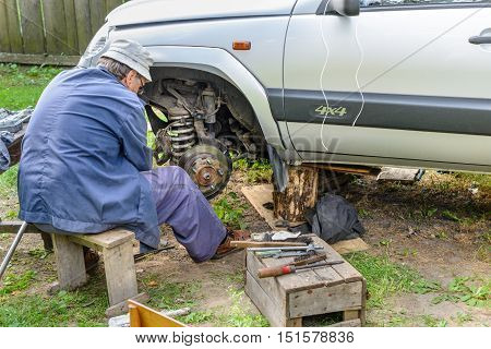 Senior Mechanic Replaces The Vehicle's Front Wheel.