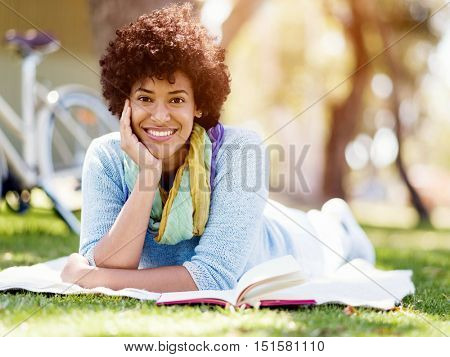 Beautiful woman laying down in summer park