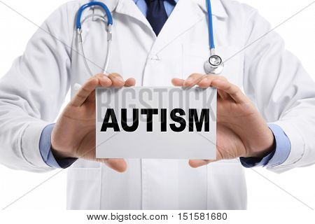 Children autism concept. Male doctor holding paper on white background, closeup