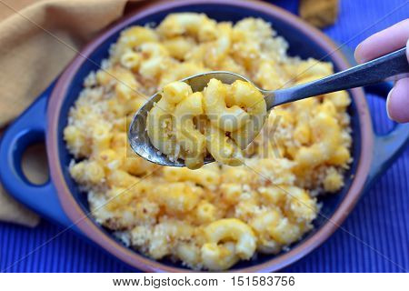 Macaroni and Cheese: Close up of hand holding spoon of cheesy noodles. Focus is on spoonful of mac and cheese.