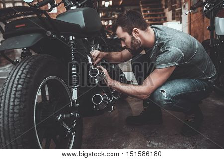 Man fixing bike. Confident young man repairing motorcycle near his garage