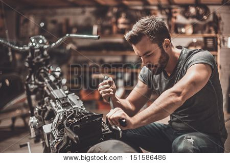 This bike should be perfect. Confident young man repairing motorcycle in repair shop