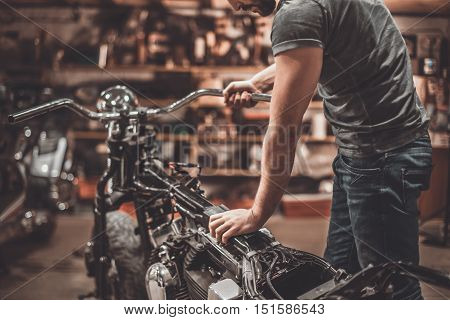 Man examining motorcycle. Close-up of young man examining motorcycle in repair shop