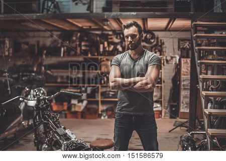 This is my place! Confident young man keeping arms crossed and looking at camera while standing near his motorcycle in garage or repair shop