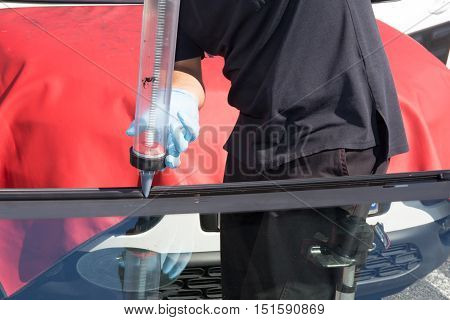 Real Mechanics changing the broken windshield of car in Auto Repair Shop