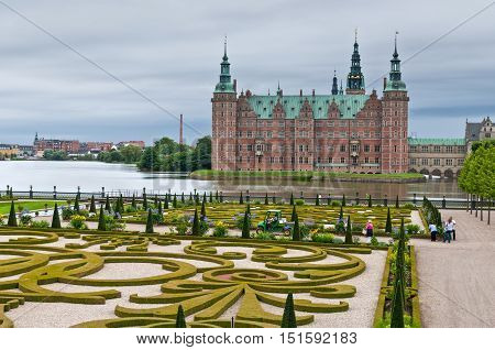 Hillerod Denmark - August 06 2010: Tourists visiting the Frederiksborg palace and the baroque gardens at nasty weather. The palace dates back to the 16th century and now houses The Museum of National History in Hillerod Denmark on August 06 2010.