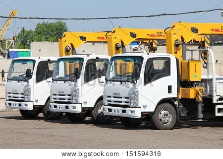 White Isuzu flatbed trucks with yellow crane arm is in the parking lot - Russia Moscow 30 August 2016
