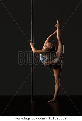 Pole dance. Image of flexible girl doing vertical split