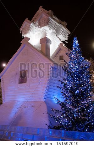 Christmas decorations: log snowy terem and lit Christmas tree lights. The photo was taken in Russia on the main square of Yekaterinburg.